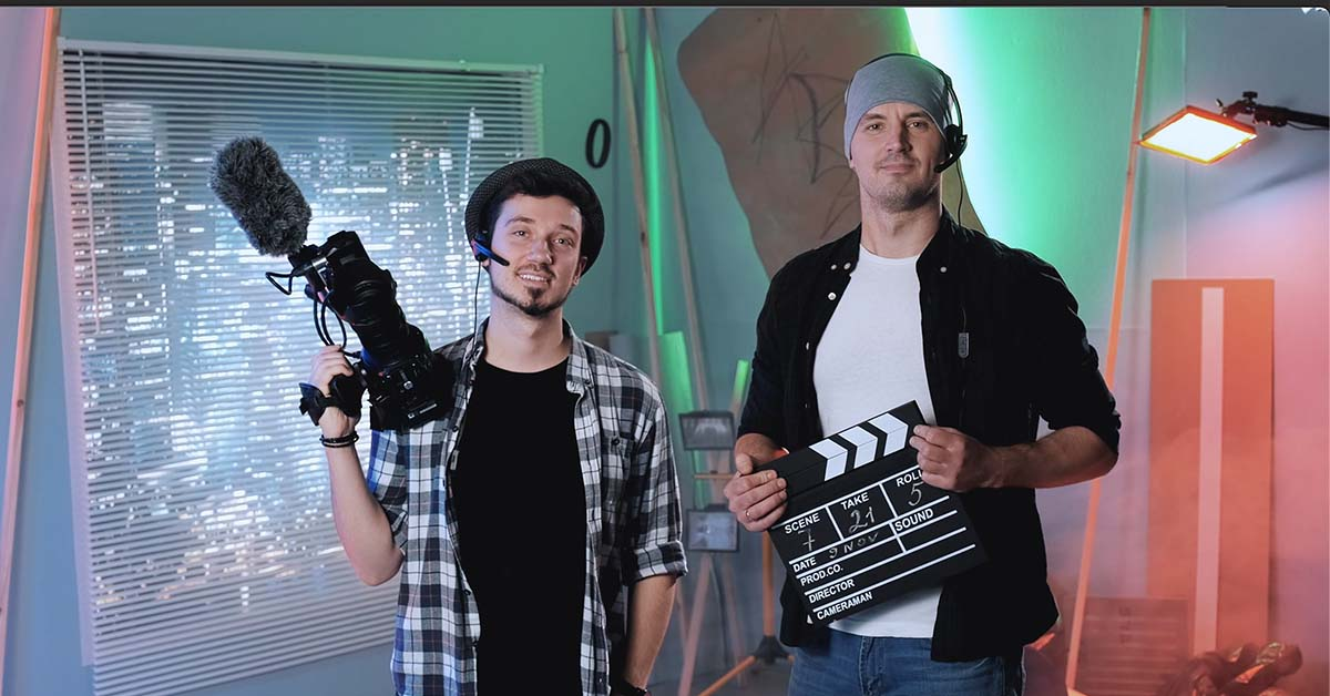 video production team with a director camera person and a sound person smiling